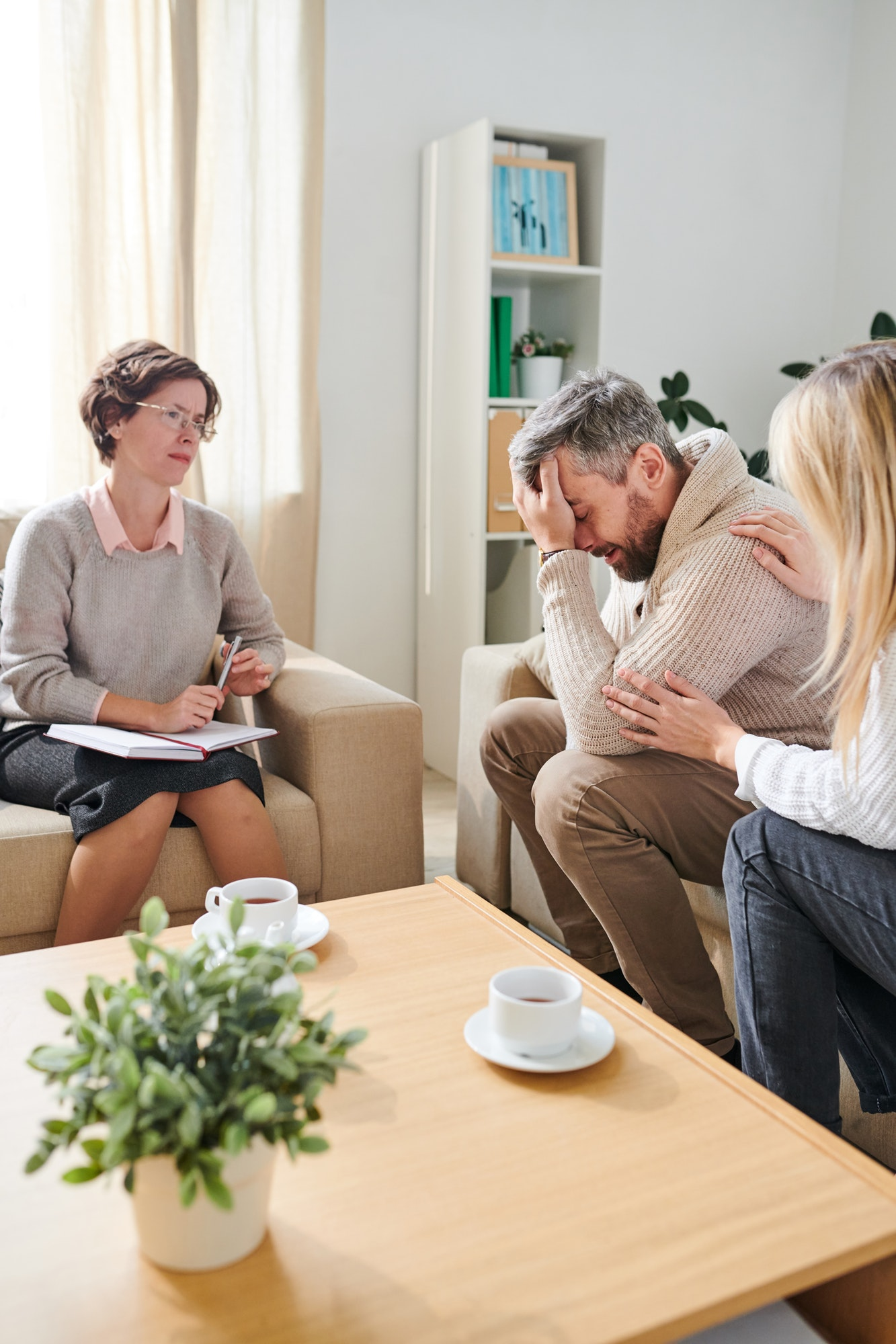 Frustrated man crying while wife supporting him at therapy sessi